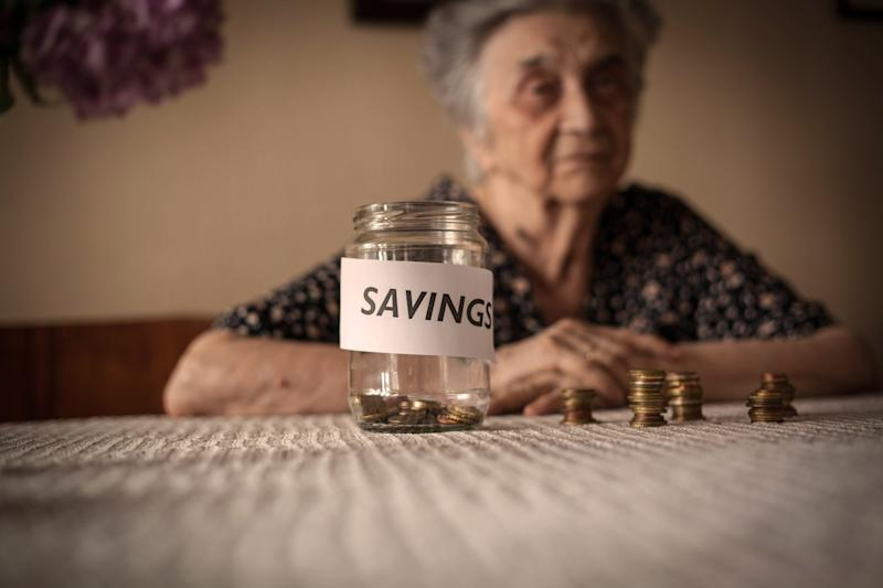 """Elderly woman with near-empty jar marked """"SAVINGS"""" sitting in front of her on the table"""