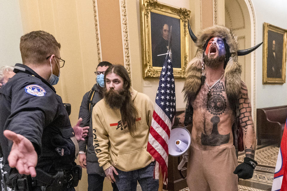 FILE - In this Wednesday, Jan. 6, 2021 file photo, supporters of President Donald Trump, including Jacob Chansley, right with fur hat, are confronted by U.S. Capitol Police officers outside the Senate Chamber inside the Capitol in Washington. A judge ordered corrections authorities to provide organic food to an Arizona man who is accused of participating in the insurrection at the U.S. Capitol while sporting face paint, no shirt and a furry hat with horns. (AP Photo/Manuel Balce Ceneta, File)