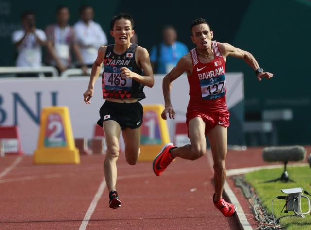 Bahrain's Elhassan Elabbassi, right, stumbles as he sprints to the finish line with Japan's Hiroto Inoue in the men's marathon at the 18th Asian Games in Jakarta, Indonesia, Saturday, Aug. 25, 2018. (AP Photo/Bernat Armangue)