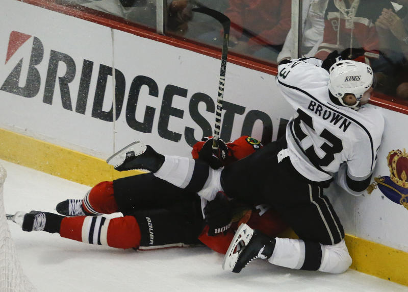 Los Angeles Kings right wing Dustin Brown (23) collides with Chicago Blackhawks defenseman Duncan Keith (2) against the boards during the first period in Game 2 of the NHL hockey Stanley Cup Western Conference finals Sunday, June 2, 2013 in Chicago. (AP Photo/Charles Rex Arbogast)