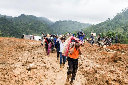 Residents carry their belongings following landslides at Cisolok district in Sukabumi, West Java province, Indonesia, January 1, 2019. Antara Foto/M Agung Rajasa/via REUTERS