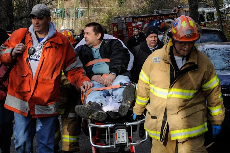 FILE - In this file photo taken on Sunday, Dec. 1, 2013, Metro North Railroad engineer William Rockefeller is wheeled on a stretcher away from the area where the commuter train he was operating derailed in the Bronx borough of New York. The engineer driving the commuter train that went off the rails in New York City last weekend has been suspended without pay according to a spokesman for Metro-North Railroad Thursday Dec. 5, 2013. (AP Photo/Robert Stolarik, File)