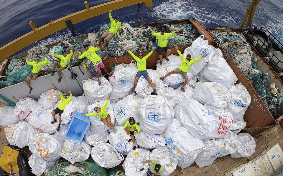 In this April 21, 2021 photo provided by Andy Carre, workers with the Papahanaumokuakea Marine Debris Project pose on top of fishing nets and plastics collected from the the beaches of the Northwestern Hawaiian Islands before offloading the marine debris in Honolulu. A crew has returned from the remote Northwestern Hawaiian Islands with a boatload of marine plastic and abandoned fishing nets that threaten to entangle endangered Hawaiian monk seals and other marine animals on the tiny, uninhabited beaches stretching for more than 1,300 miles north of Honolulu. (Andy Carre, Papahanaumokuakea Marine Debris Project via AP)