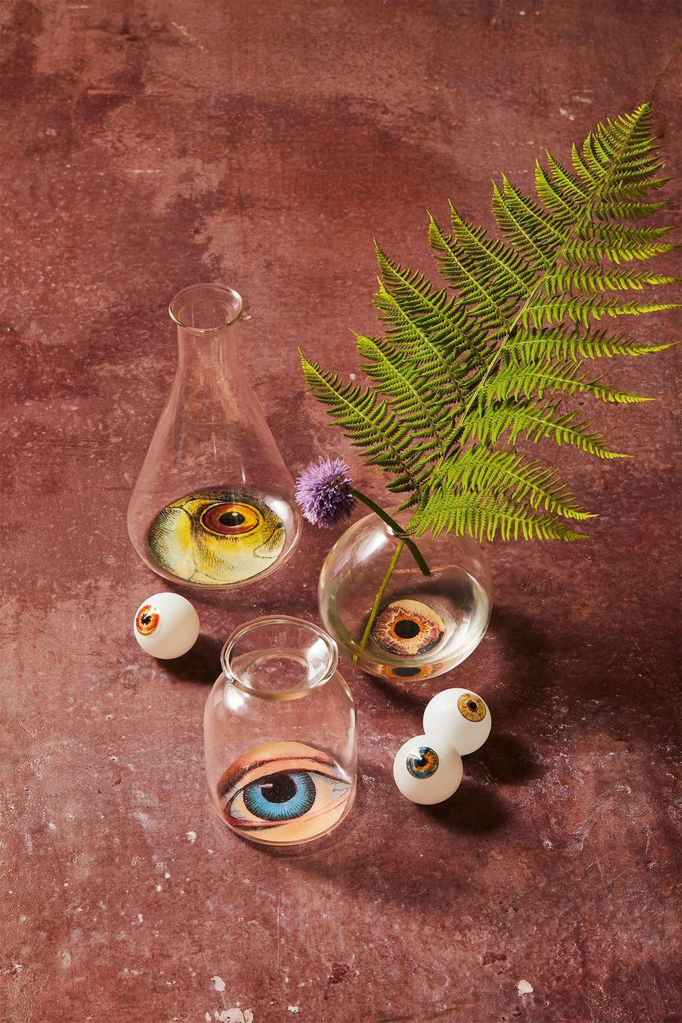 """<p>Use these eerie vessels as vases, or as cocktail glasses (they're food safe as long as the liquid doesn't come in contact with the decoupaged artwork). Gather a mix of clean recycled bottles and jars, <a href=""""https://www.jamaligarden.com/4in-smoke-ball-bud-vase.html"""" rel=""""nofollow noopener"""" target=""""_blank"""" data-ylk=""""slk:bud vases"""" class=""""link rapid-noclick-resp"""">bud vases</a> and chemistry <a href=""""https://www.jamaligarden.com/6in-lab-glass-bud-vase-set-of-4.html"""" rel=""""nofollow noopener"""" target=""""_blank"""" data-ylk=""""slk:flasks"""" class=""""link rapid-noclick-resp"""">flasks</a>, then <a href=""""https://hmg-prod.s3.amazonaws.com/files/gh-halloween-artwork-1597083176.pdf?tag=syn-yahoo-20&ascsubtag=%5Bartid%7C10055.g.33437890%5Bsrc%7Cyahoo-us"""" rel=""""nofollow noopener"""" target=""""_blank"""" data-ylk=""""slk:download our eyeball clip art"""" class=""""link rapid-noclick-resp"""">download our eyeball clip art</a> and print onto regular printer paper. Cut out the eye shapes to fit to the bottom of the jars. Paint a thin layer of Mod Podge to the bottom exterior of the glass and place your cut paper (artwork-side down) on top. Smooth out any air bubbles or wrinkles with your fingers and let dry. Paint on a couple additional layers of Mod Podge to seal and let dry several hours. <br></p>"""