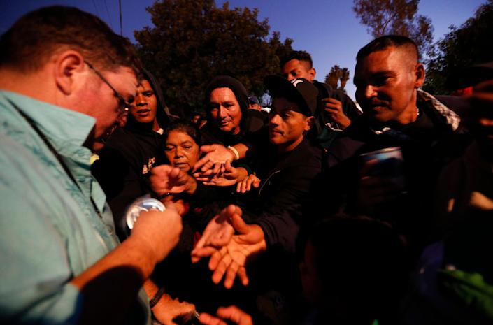 An American well-wisher, left, is swarmed by migrants as he hands out canned soup, adding his efforts to those of many local Mexican groups distributing food outside of a sports complex where more than 5,000 Central Americans are sheltering in Tijuana, Mexico. (Photo: Rebecca Blackwell/ASSOCIATED PRESS)