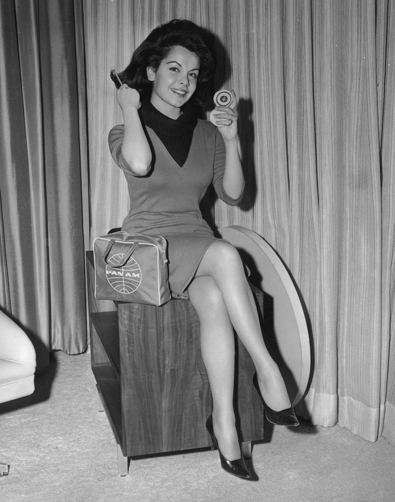 circa 1963:  American actor and singer Annette Funicello smiles and brushes her hair using a compact prior to embarking on a European publicity tour for director William Asher's film, 'Muscle Beach Party,' John F. Kennedy International Airport, New York City. A small Pan Am travel bag sits beside her.  (Photo by Hulton Archive/Getty Images)