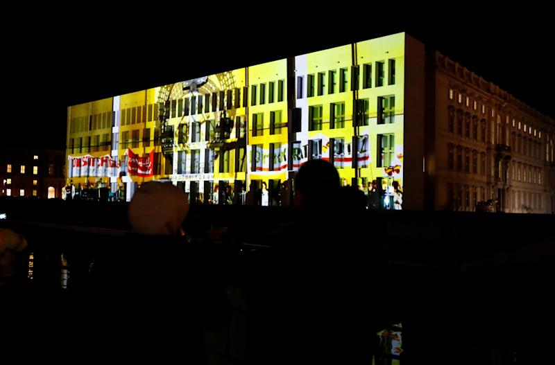 People stand in front of a projection on the construction site of the Berliner Schloss - Humboldtforum in Berlin, Germany, November 4, 2019. On November 9th Germany will mark the 30th anniversary of the fall of the Berlin Wall (Berliner Mauer) in 1989. REUTERS/Fabrizio Bensch