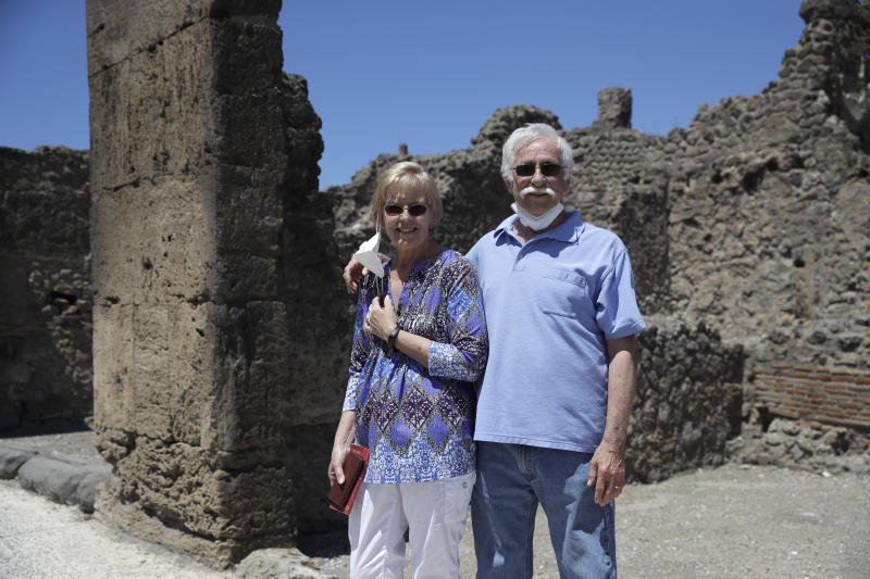 Colleen and Marvin Hewson, from the United States, pose for a photograph during their visit to the archeological sites of Pompeii, near Naples, southern Italy, Tuesday, May 26, 2020. An American couple waited a lifetime plus 2 ½ months to visit the ancient ruins of Pompeii together. For Colleen and Marvin Hewson, the visit to the ruins of an ancient city destroyed in A.D. 79 by a volcanic eruption was meant to be the highlight a trip to celebrate his 75th birthday and their 30th anniversary. They were among the only tourists present when the archaeological site reopened to the public on Tuesday after the national lockdown to prevent the spread of COVID-19.  (AP Photo/Alessandra Tarantino)