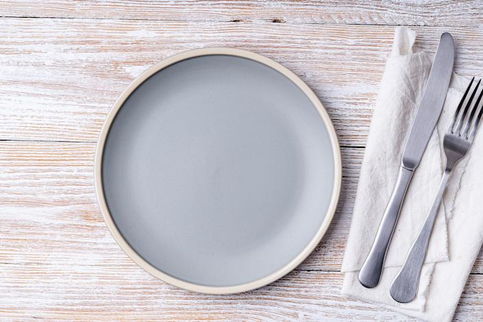 Empty ceramic plate, fork and knife on linen napkin,  rural wooden background. Top view with copy space