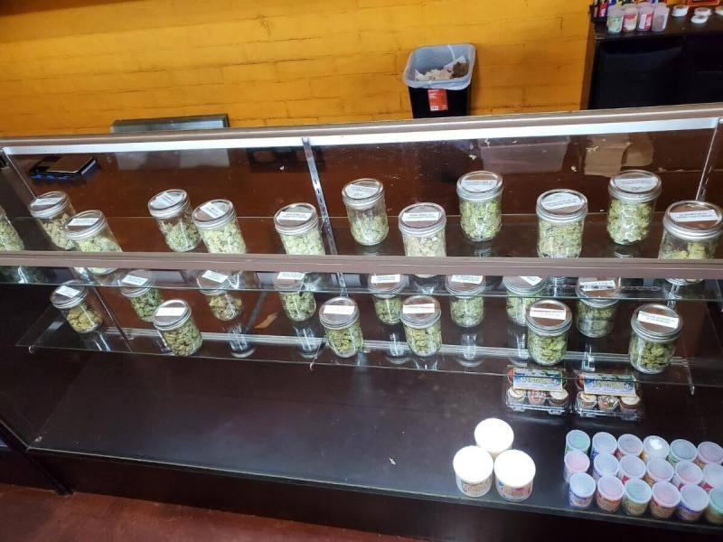 This Thursday, Dec,. 12, 2019 photo provided by the Department of Consumer Affairs shows a display with jars of marijuana at Save Greens Cannabis dispensary in Los Angeles. California regulators mounted two-dozen raids against illegal marijuana retailers in Los Angeles this week, the largest crackdown to date against the city's thriving illicit pot market, officials announced Friday, Dec. 13, 2019.  (Megan Kiefer/Department of Consumer Affairs via AP)