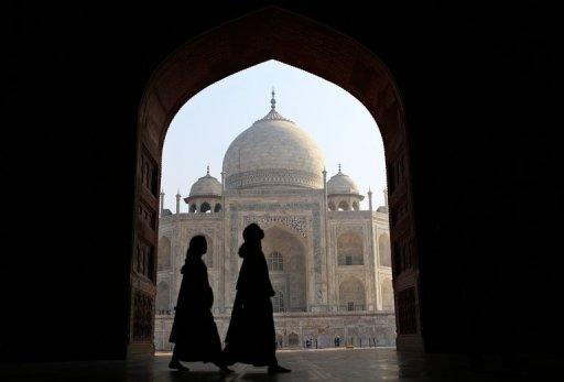 <p>Women tourists walk past an archway at the historic Taj Mahal in Agra on November 28, 2012. The Associated Chambers of Commerce and Industry of India (ASSOCHAM) says overall tourist arrivals are down 25 percent year-on-year, with holidaymakers opting instead to visit other Asian countries such as Malaysia and Thailand.</p>