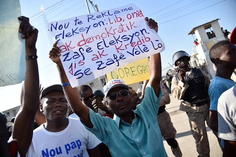Demonstrators hold up signs during a protest near the parliament in Port-au-Prince, on December 8, 2016 (AFP Photo/Hector Retamal)