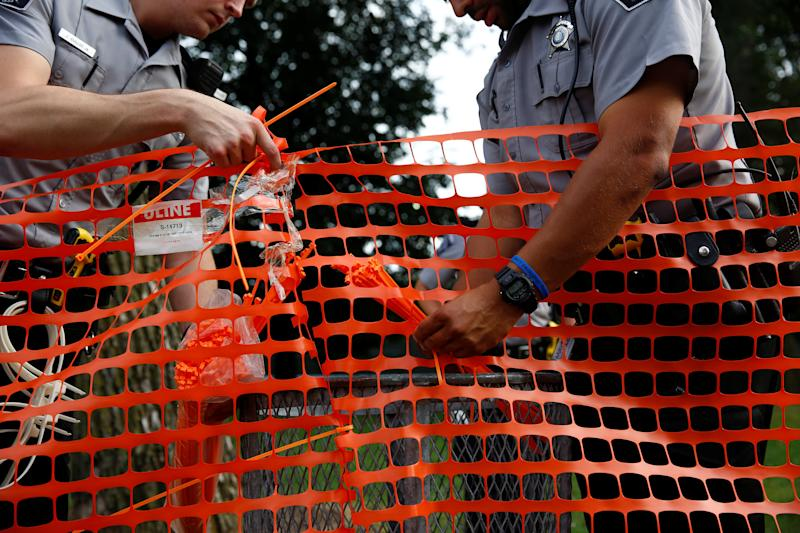 Members of the Milwaukee County Sheriff's department erect a fence around Sherman Park after disturbances following the police shooting of a man in Milwaukee, Wisconsin, U.S. August 15, 2016. REUTERS/Aaron P. Bernstein