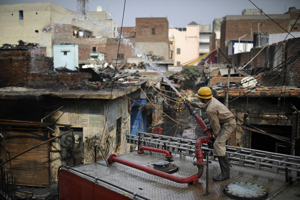 Fire fighters douse a fire at Gokul Puri tyre market which was burnt Tuesday's violence in New Delhi, India, Wednesday, Feb. 26, 2020. At least 20 people were killed in three days of clashes in New Delhi, with the death toll expected to rise as hospitals were overflowed with dozens of injured people, authorities said Wednesday. The clashes between Hindu mobs and Muslims protesting a contentious new citizenship law that fast-tracks naturalization for foreign-born religious minorities of all major faiths in South Asia except Islam escalated Tuesday. (AP Photo/Altaf Qadri)