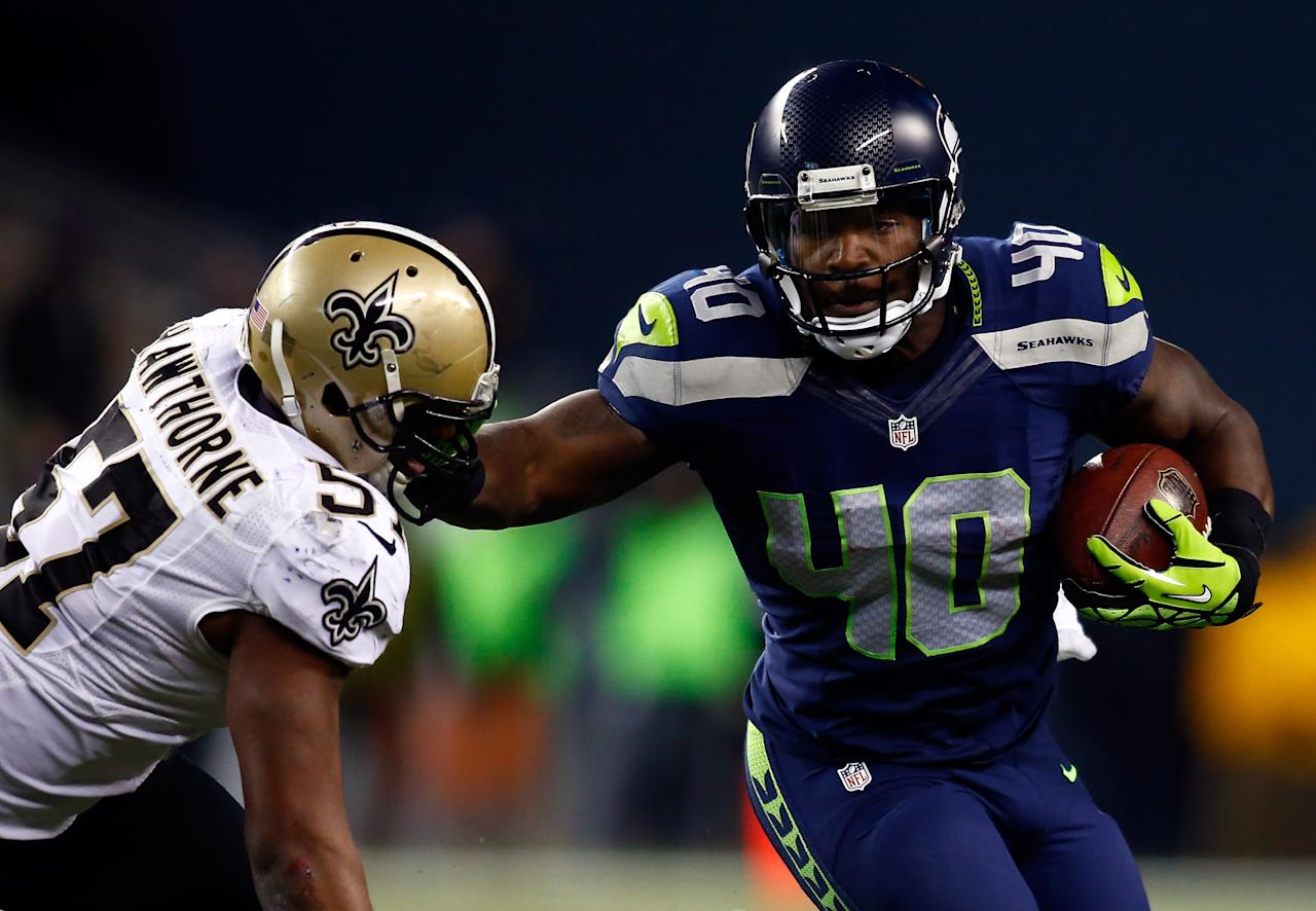 SEATTLE, WA - DECEMBER 02: Fullback Derrick Coleman #40 of the Seattle Seahawks carries the ball as outside linebacker David Hawthorne #57 of the New Orleans Saints defends during a game at CenturyLink Field on December 2, 2013 in Seattle, Washington. (Photo by Jonathan Ferrey/Getty Images)