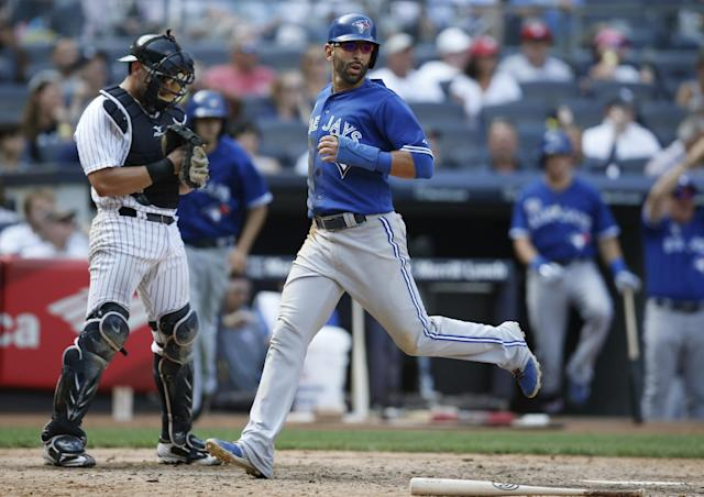 New York Yankees catcher Francisco Cervelli, left, looks down as Toronto Blue Jays Jose Bautista scores on Dioner Navarro's game-winning, ninth-inning RBI single in a baseball game against the New York Yankees at Yankee Stadium in New York, Sunday, July 27, 2014. The Jays defeated the Yankees 5-4. (AP Photo/Kathy Willens)
