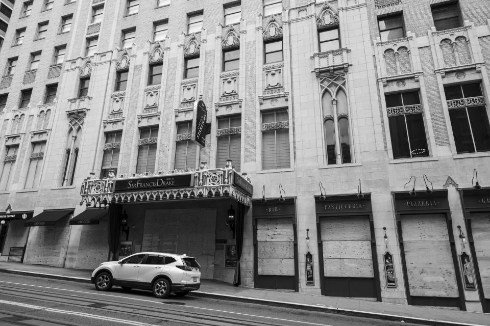 The Sir Francis Drake Hotel, known for its Beefeater doormen, is boarded up and closed at Union Square in San Francisco on April 17, 2020. Normally, the months leading into summer bring bustling crowds to the city's famous landmarks, but this year, because of the coronavirus threat they sit empty and quiet. Some parts are like eerie ghost towns or stark scenes from a science fiction movie. (AP Photo/Eric Risberg)