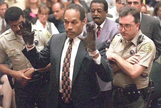 O.J. Simpson holds up his hands for the jury after trying on a pair of bloody gloves at his 1995 murder trial (AFP Photo/SAM MIRCOVICH)