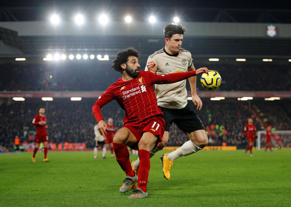 Liverpool's Mohamed Salah (front) in action with Manchester United's Harry Maguire.