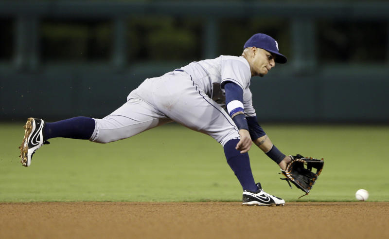 San Diego Padres shortstop Ronny Cedeno chases down a ground ball by Philadelphia Phillies' Kevin Frandsen during the fourth inning of a baseball game, Wednesday, Sept. 11, 2013, in Philadelphia. Cedeno made the play at first. (AP Photo/Matt Slocum)