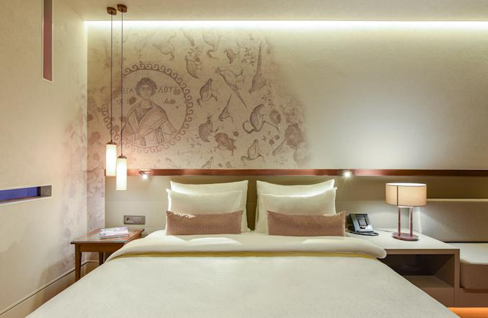 Guest rooms are minimalist with art that reflects the archaeological ruins below.