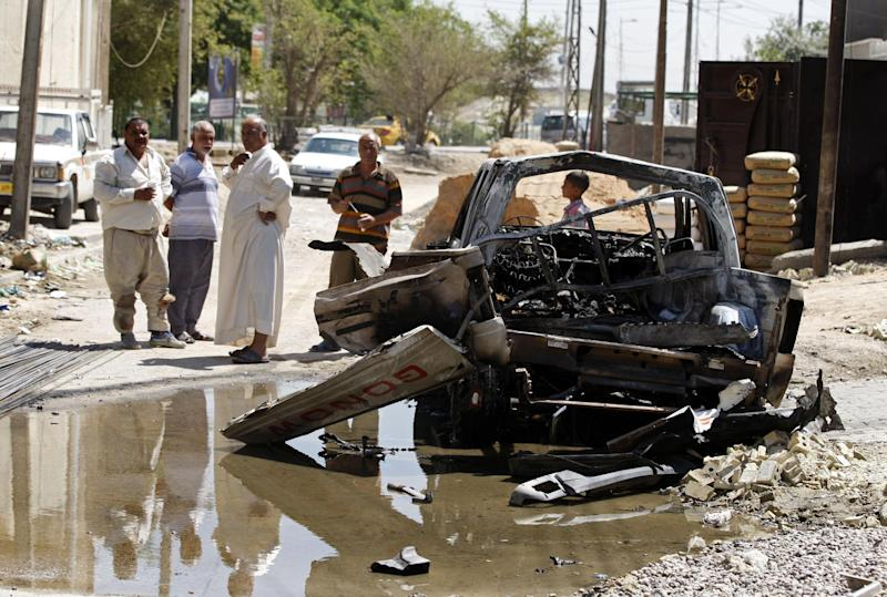 Civilians inspect the aftermath of a car bomb attack in Baghdad, Iraq, Wednesday, July 24, 2013. A bomb exploded near a Sunni mosque in Baghdad's southern Dora neighborhood on Tuesday, killing several people and wounding many more, police said. (AP Photo/Karim Kadim)