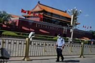 A police officer patrols in Tiananmen Square in front of a portrait of late Chinese chairman Mao Zedong in Beijing