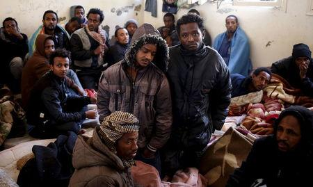 Illegal migrants sit in an immigration holding centre located on the outskirts of Misrata