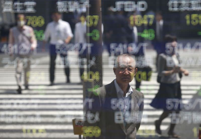 People are reflected on a stock quotation board outside a brokerage in Tokyo May 7, 2014. REUTERS/Toru Hanai