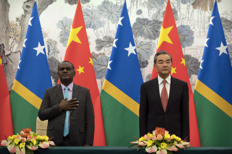 Solomon Islands Foreign Minister Jeremiah Manele, left, and Chinese Foreign Minister Wang Yi stand during the Solomon Islands national anthem at a ceremony to mark the establishment of diplomatic relations between the Solomon Islands and China at the Diaoyutai State Guesthouse in Beijing, Saturday, Sept. 21, 2019. (AP Photo/Mark Schiefelbein, Pool)