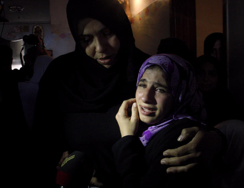 A Palestinian woman comforts another during the funeral of Matar Abu Ata, 20, killed in an overnight Israeli airstrike in Gaza City, Sunday, Nov. 11, 2012. While cross-border fighting is a common occurrence, hostilities spiraled sharply over the weekend, with bombardments from Gaza causing rare Israeli casualties and Israeli strikes killing at least six Palestinians. (AP Photo/Hatem Moussa)