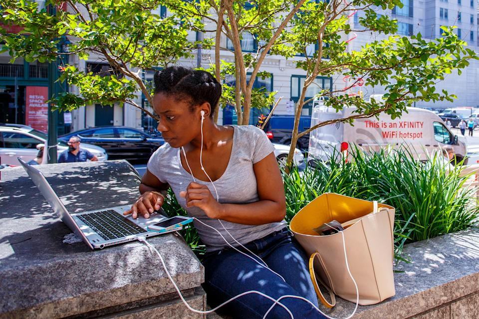 Dajae Gilliard uses her mobile phone and laptop in Philadelphia. (Photo: Jeff Fusco/AP Images for Comcast)