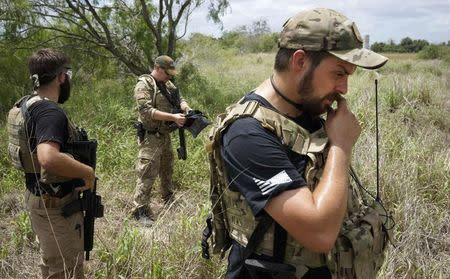 "Members of the ""Patriots"" (L-R) Huggie Bear (not his real name), Will (no last name given) and Rob Chupp patrol on the U.S.-Mexico border outside Brownsville, Texas September 2, 2014. REUTERS/Rick Wilking"