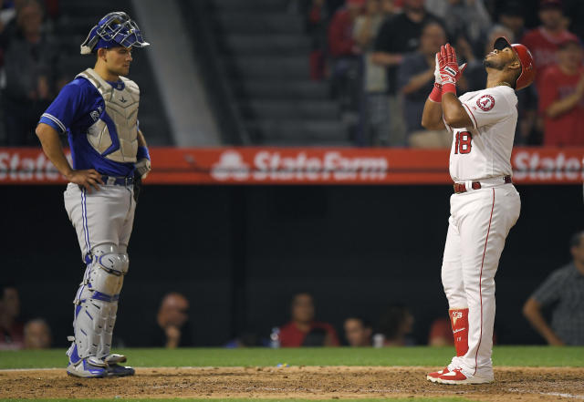 Los Angeles Angels' Luis Valbuena, right, gestures after hitting a two-run home run as Toronto Blue Jays catcher Luke Maile stands at the plate during the fifth inning of a baseball game Thursday, June 21, 2018, in Anaheim, Calif. (AP Photo/Mark J. Terrill)