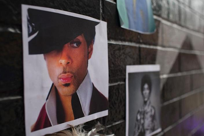 Photos of Prince attached to the wall outside of the First Avenue nightclub where fans have created a memorial to the artist on April 22, 2016 in Minneapolis (AFP Photo/Scott Olson)