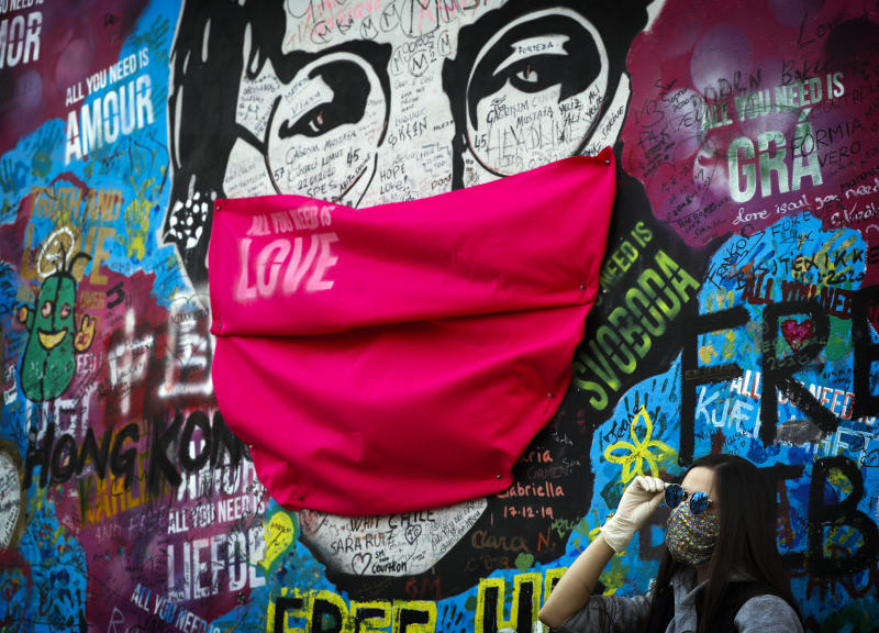 """A woman poses for a photo by the """"Lennon Wall"""" with a face mask attached to the image of John Lennon, in Prague, Czech Republic, Monday, April 6, 2020. (AP Photo/Petr David Josek)"""
