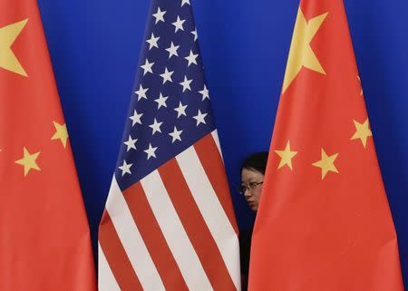 A member of staff from Chinese government adjusts U.S. and Chinese national flags in Beijing
