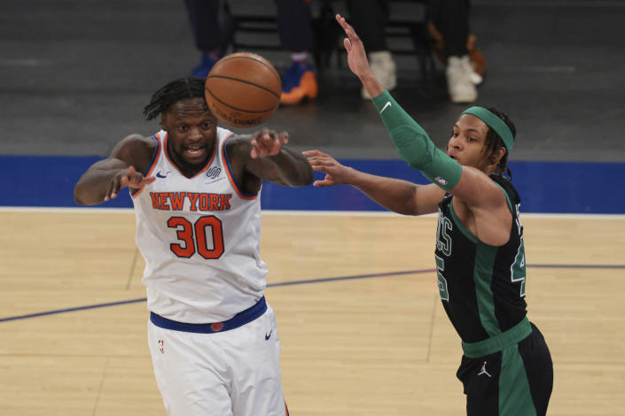 New York Knicks forward Julius Randle (30) passes the ball against Boston Celtics guard Romeo Langford (45) during the second half of an NBA basketball game in New York, Sunday, May 16, 2021. (Vincent Carchietta/Pool Photo via AP)