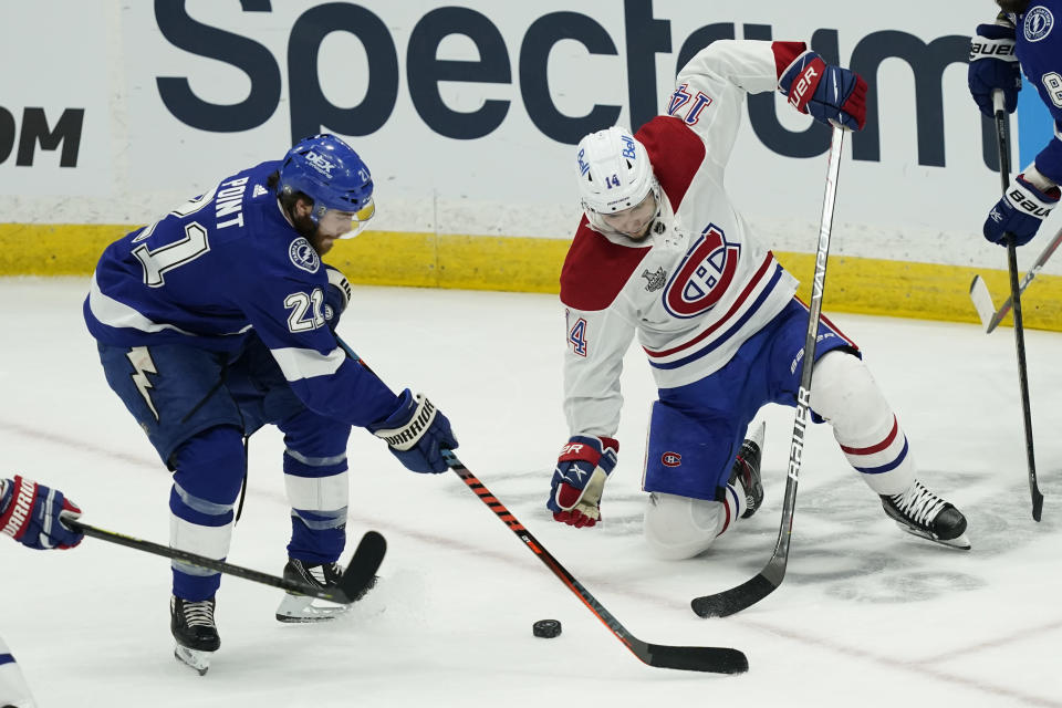 Tampa Bay Lightning center Brayden Point (21) and Montreal Canadiens center Nick Suzuki (14) play the puck during the second period in Game 1 of the NHL hockey Stanley Cup finals, Monday, June 28, 2021, in Tampa, Fla. (AP Photo/Gerry Broome)