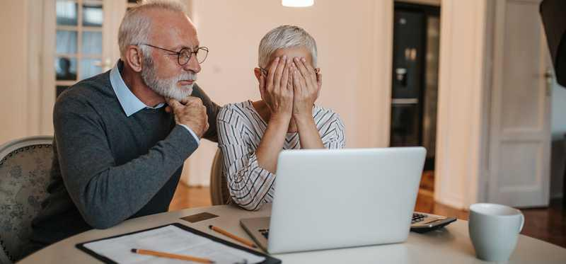 An elderly couple look at a laptop screen, the wife covers her face.