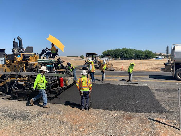 TechniSoil workers get the newly repaved road ready before the steam roller flattens it.