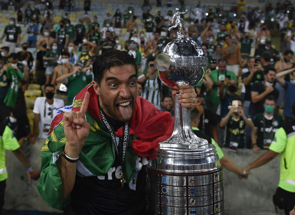 Coach Abel Ferreira of Brazil's Palmeiras celebrates with the trophy after winning the Copa Libertadores final soccer match against Brazil's Santos at the Maracana stadium in Rio de Janeiro, Brazil, Saturday, Jan. 30, 2021. Palmeiras won 1-0. (Mauro Pimentel/Pool via AP)