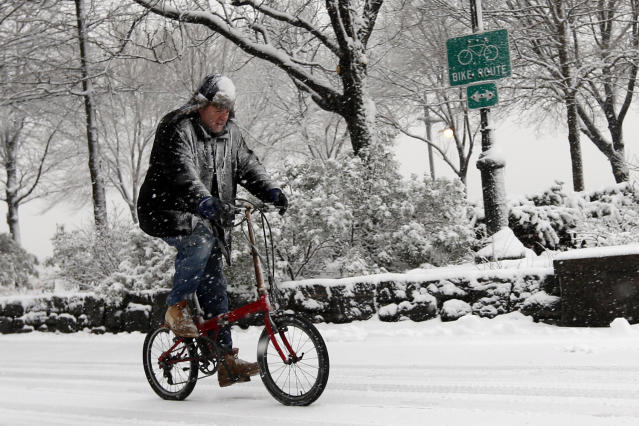 A cyclist makes his way up the Hudson River Greenway as heavy snow falls Monday, Feb. 3, 2014, in New York. (AP Photo/Jason DeCrow)