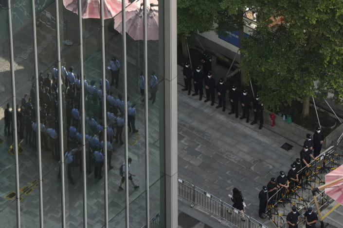 Chinese police and security personnel prepare for duty outside the Evergrande headquarters in Shenzhen, China, Friday, Sept. 24, 2021. Things appeared quiet at the headquarters of the heavily indebted Chinese real estate developer Evergrande, one day after the day it had promised to pay interest due to bondholders in China. (AP Photo/Ng Han Guan)