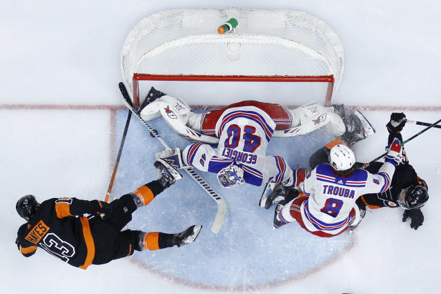 New York Rangers' Alexandar Georgiev (40) blocks a shot by Philadelphia Flyers' Kevin Hayes (13) as Jacob Trouba (8) and Travis Sanheim (6) battle during the second period of an NHL hockey game, Friday, Feb. 28, 2020, in Philadelphia. (AP Photo/Matt Slocum)