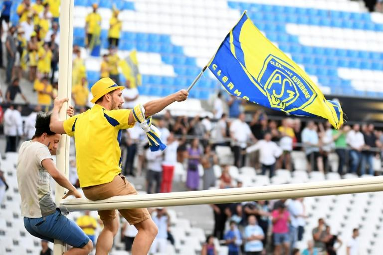 Clermont's supporters climb goal posts after Clermont defeated Racing 92, 37-31 at the French Top 14 rugby union semi-final match on May 27, 2017 in Marseille France
