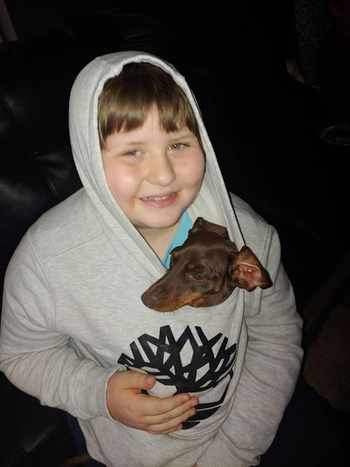 Gage Andrews, 9, shown with his dog Angel, is at the center of a new lawsuit alleging years of abuse by his former special education teacher in Statesville.