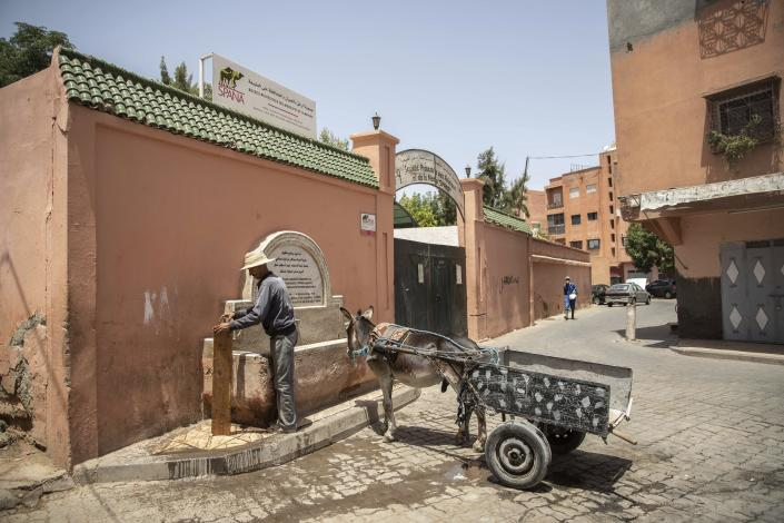 A merchant stops his donkey cart at a water fountain on a hot summer day in Marrakech, Morocco, Wednesday, July 22, 2020. Morocco's restrictions to counter the coronavirus pandemic have taken a toll on the carriage horses in the tourist mecca of Marrakech. Some owners struggle to feed them, and an animal protection group says hundreds of Morocco's horses and donkeys face starvation amid the collapsing tourism industry. (AP Photo/Mosa'ab Elshamy)