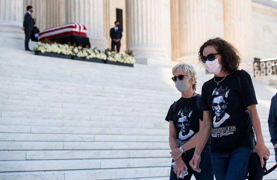 "<p>Members of the public wearing ""Notorious RBG"" t-shirts, walk past the casket of the late Supreme Court Justice Ruth Bader Ginsburg on the steps of the US Supreme Court in Washington, DC, September 23, 2020.</p>"