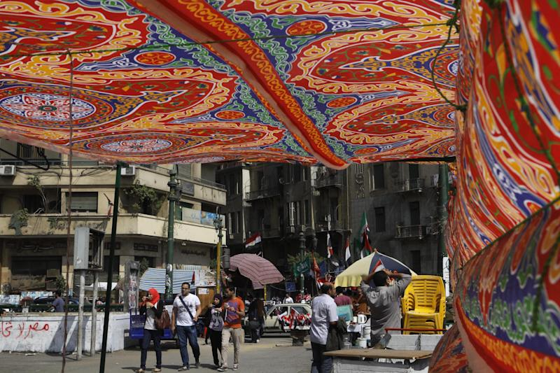 Egyptians looks through a decorated tent set by volunteers to offer a shade spot in Tahrir Square, the focal point of Egyptian uprising in Cairo, Egypt, Tuesday, June 18, 2013. Temperatures in Cairo reached 34 degrees Celsius (93 degrees Fahrenheit). (AP Photo/Amr Nabil)